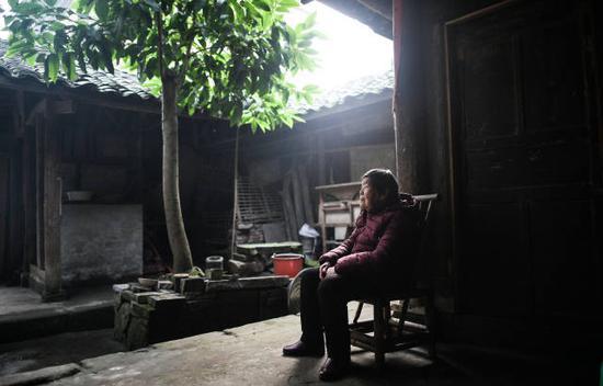 1月21日,在四川泸县方洞镇,86岁的艾秀平坐在堂屋的竹椅上,痴痴地向门外张望,等待儿子回家。 新华社记者薛玉斌摄