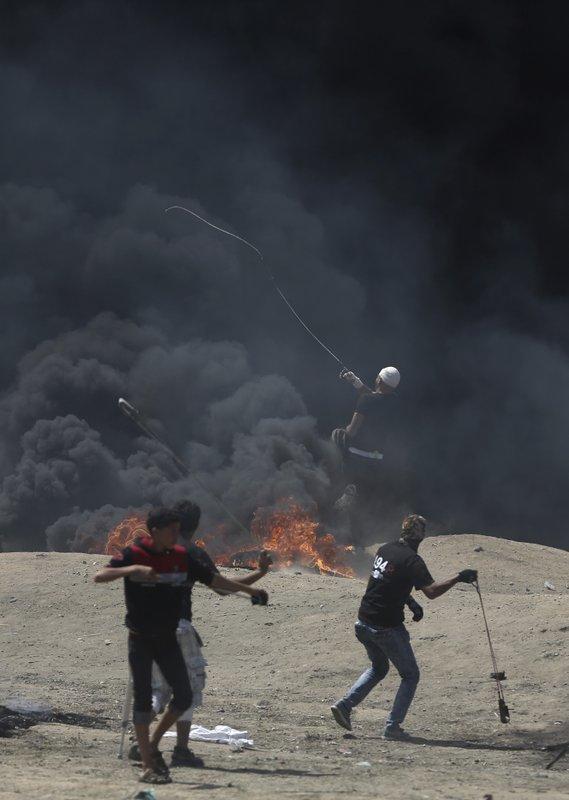 图为巴勒斯坦抗议民众14日向以色列军队扔石头。(美联社)