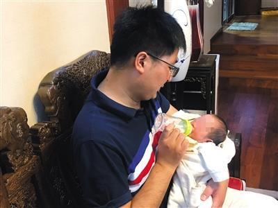 8月16日,王柯丁在家中给孩子喂奶。新京报记者 周小琪 摄